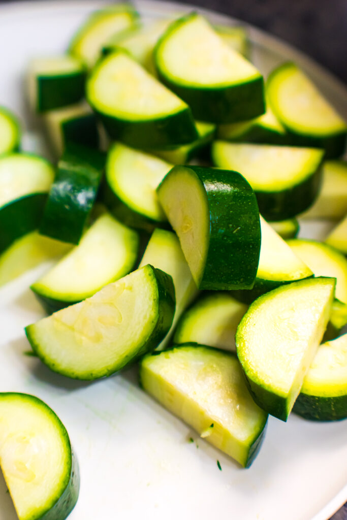 Sliced zucchini wedges on a white plate.