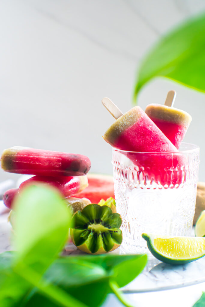 Watermelon Kiwi Ice Pops stack with sliced kiwi and lime in the foreground.
