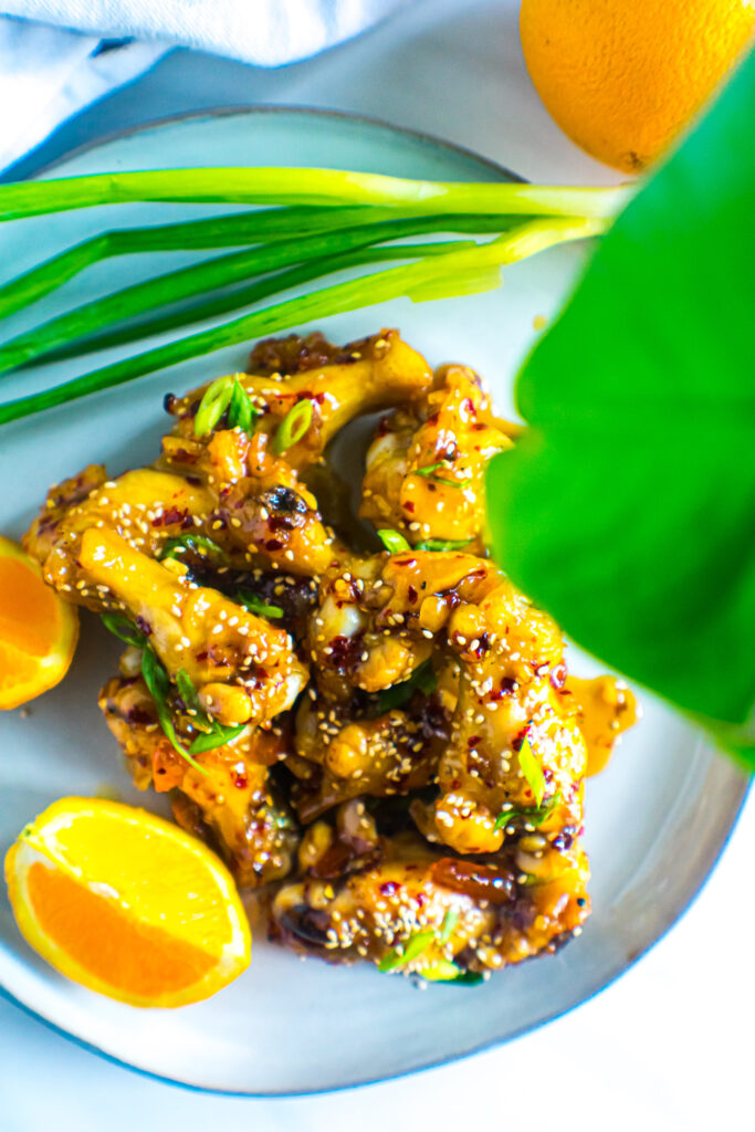 Oven baked orange chicken wings on a grey plate with slice oranges and a green onion stalk.